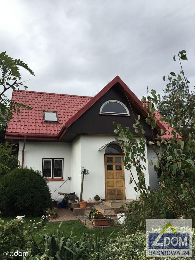 Mały biały domek w dużym ogrodzie