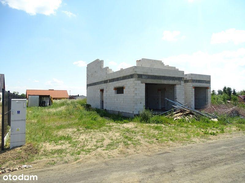 Działka budowlana z rozpoczętą budową domu.