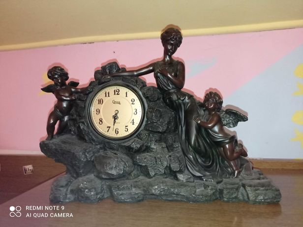 Zegar, rzeźba kobiety i aniołów