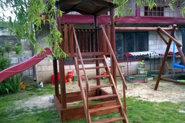 Drewniany domek dla dzieci z huśtawką, piaskownicą i zjeżdżalnią