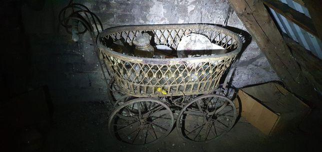 Wózek dziecięcy z lat 30 (kosz Mojżesza) wiklinowy na dużych kołach.
