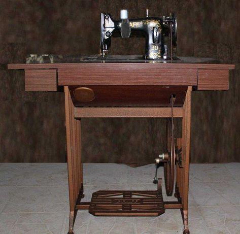 Máquina de costura antiga da PFAFF com mesa a trabalhar