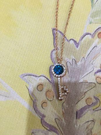 Colar/fio dourado com uma chave com pedra azul