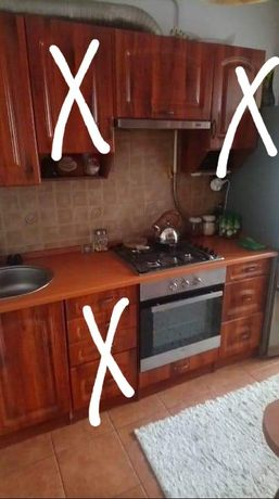 Meble kuchenne z płytą gazową, piekarnikiem, okapem i zlewem.