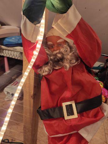 Duży Mikołaj wspinajacy się na linie LED