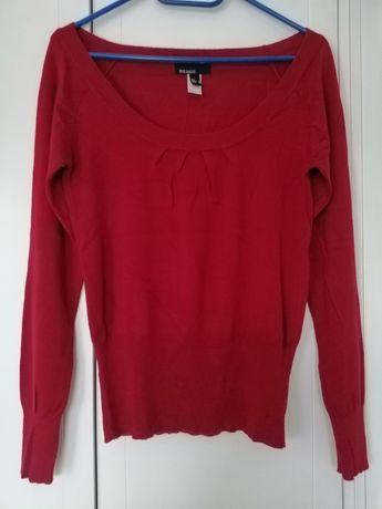 Czerwony sweter z dekoltem.