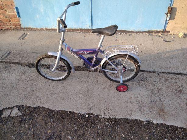 Детский велосипед с боковыми колесами.