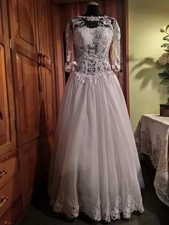 Śliczna bogato zdobiona koronką suknia ślubna z długim welonem