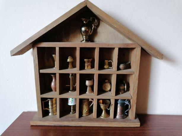 Drewniana witryna w kształcie domku z mosiężnymi miniaturkami