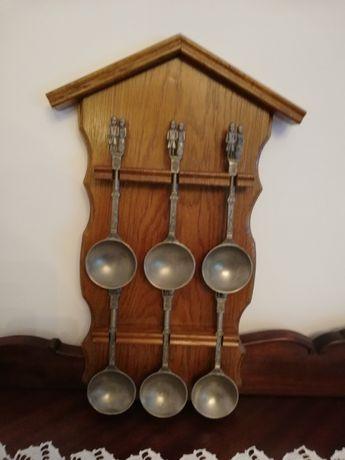 Peça em madeira castanha com seis colheres decorativas para parede