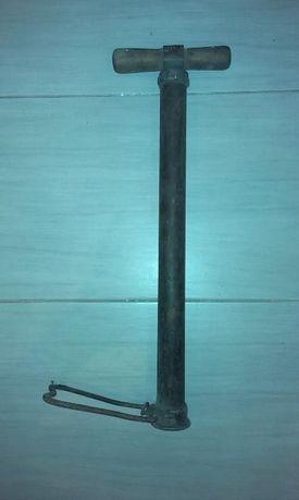 Zabytek - stara pompka z drewnianą rączką do pompowania powietrza.