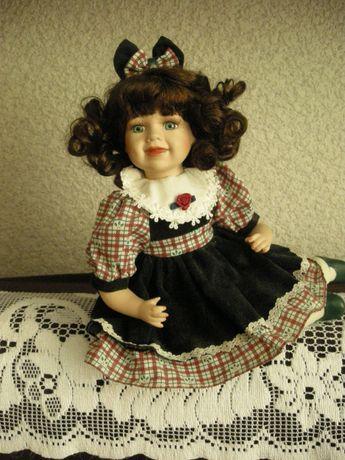 lalka porcelanowa, siedząca, brunetka, wys. 25 cm szer. 29 cm