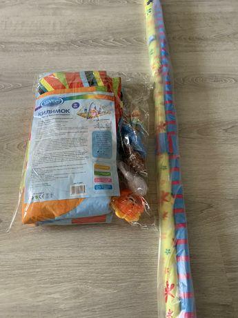 Продам новый коврик Lindo с дугами и подвесными игрушками