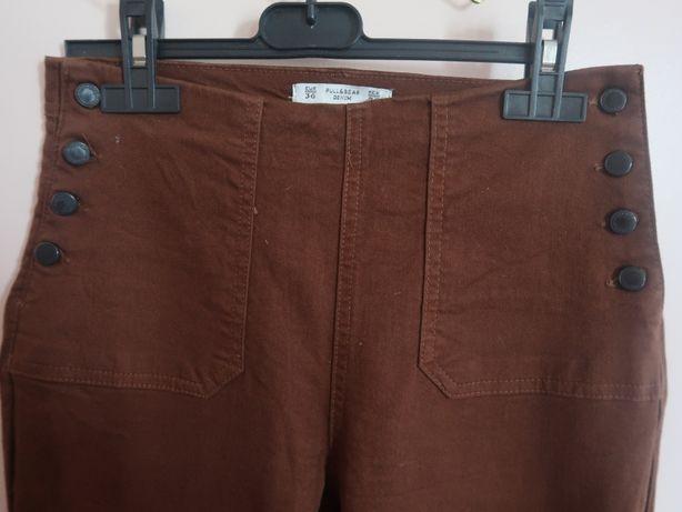 Calças de cor castanha, de cinta subida, com botões de lado