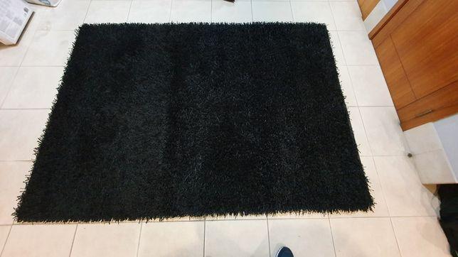 Carpete preta de pêlo longo.