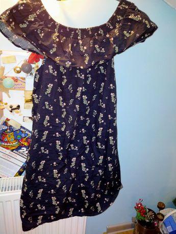 Długa sukienka w kwiecisty wzór noszona na ramionach
