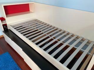 Cama de solteiro, duas caixas de arrumação e arrumação de parede