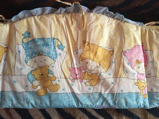 Защита бортика на кроватку и карманы для аксессуаров.