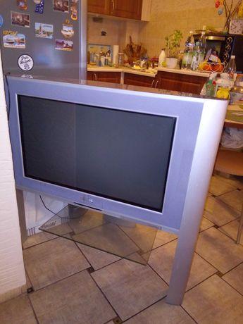 Telewizor na nóżkach ze szklaną półką.