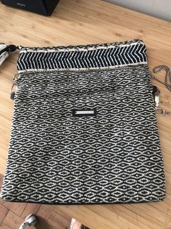 Carteira de tecido com uma parte bordada, a preto e branca