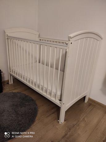 Białe łóżeczko z materacem