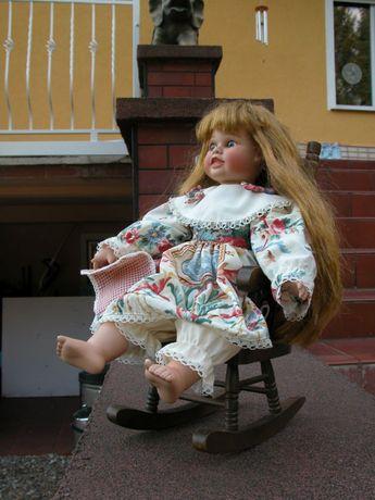 lalka porcelanowa w foteliku