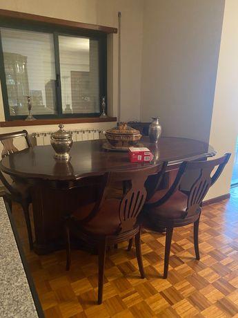 Mesa de madeira escura com 4 cadeiras do mesmo feitio