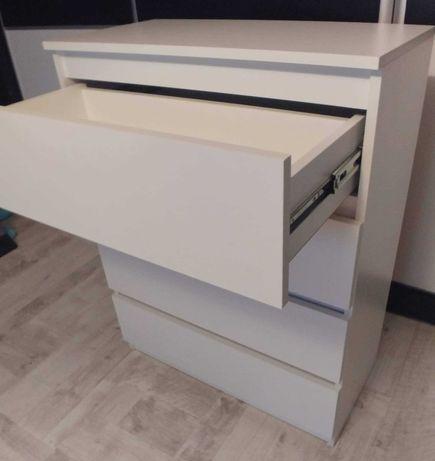 Biała komoda z szufladami.