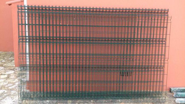 Seis paineis vedação de malha verde e quatro postes metálicos verdes.