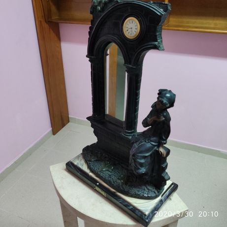 Estátua com espelho e relógio