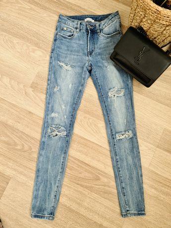 Spodnie jeansy rurki z dziurami