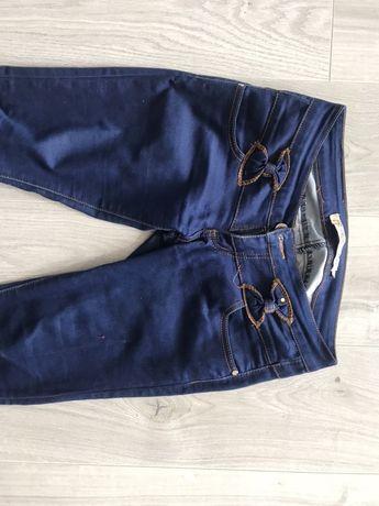 Damskie spodnie rurki jensowe kokardki ciemny niebieski kolor granatow