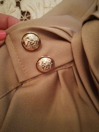 Calças beges com botões dourados