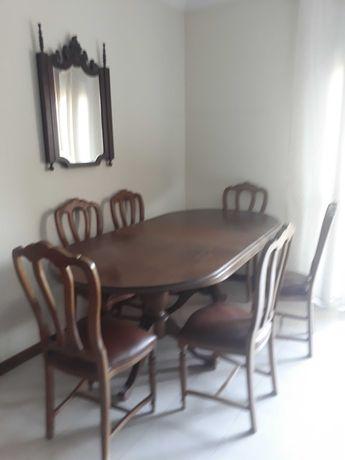 Mesa em madeira com 6 cadeiras estofadas em couro.