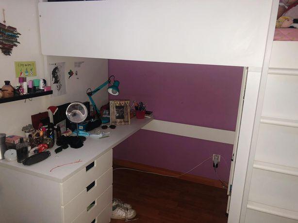 Cama alta, com secretária, um armário e colchão.