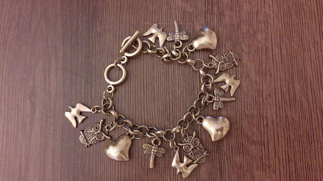 Metalowa bransoletka w kolorze złota, z zawieszkami