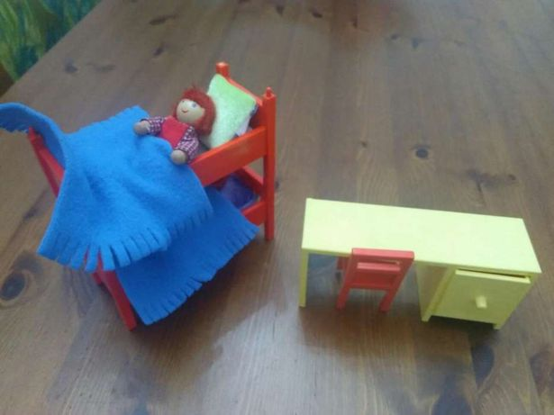 Quarto com camas de beliche e secretaria para bonecos pequenos.