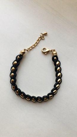 Czarna bransoleta ze złotymi zdobieniami