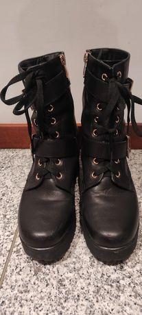 Botas pretas com tachas e cordões