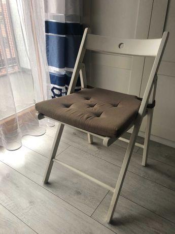 Dwa białe składane krzesła z poduszkami Ikea