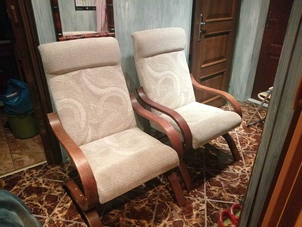 Dwa fotele beżowe obicie, drewno brązowe.