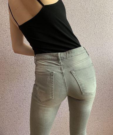 серые джинсы с заклепками и замочками внизу на средней посадке