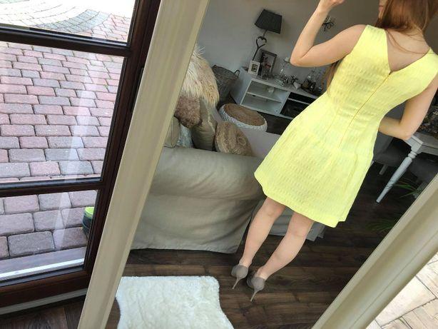 żółta sukienka z lekko uwidocznionymi plecami