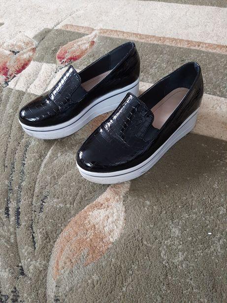 Чорне лакове взуття.