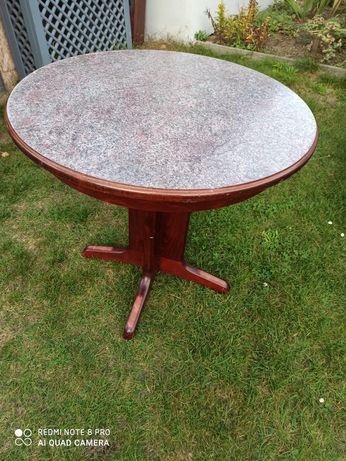 Stół okrągły na drewnianych nogach.