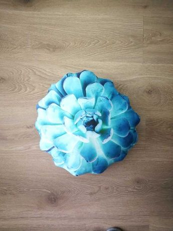 almofada redonda azul, com motivo floral