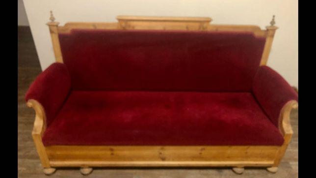 Sofa z litego drewna wykończona czerwonym materiałem welurowym