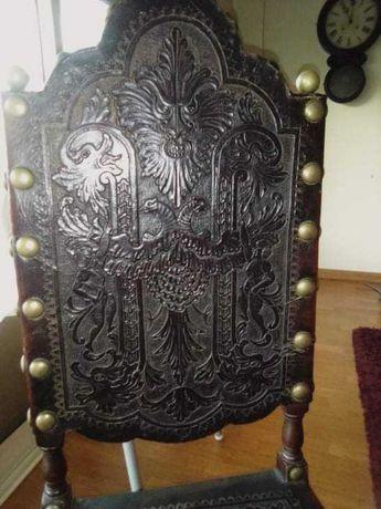 Cadeira antiga em couro, com elementos antigos.