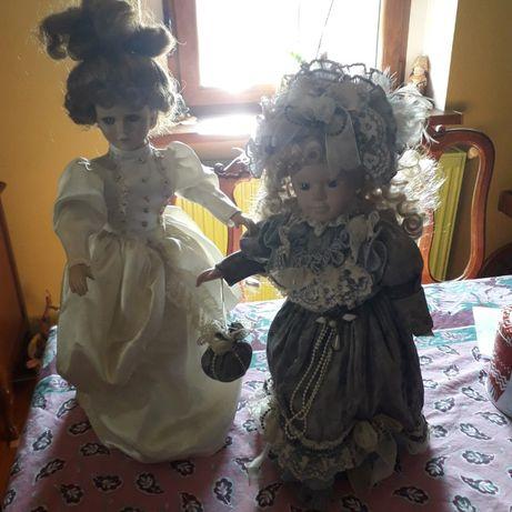 Lalki porcelanowe na metalowej podstawie.
