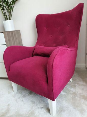 Fotel uszak tapicerowany na drewnianych nóżkach.